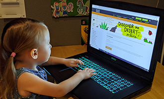 Young Girl using laptop to view online programming